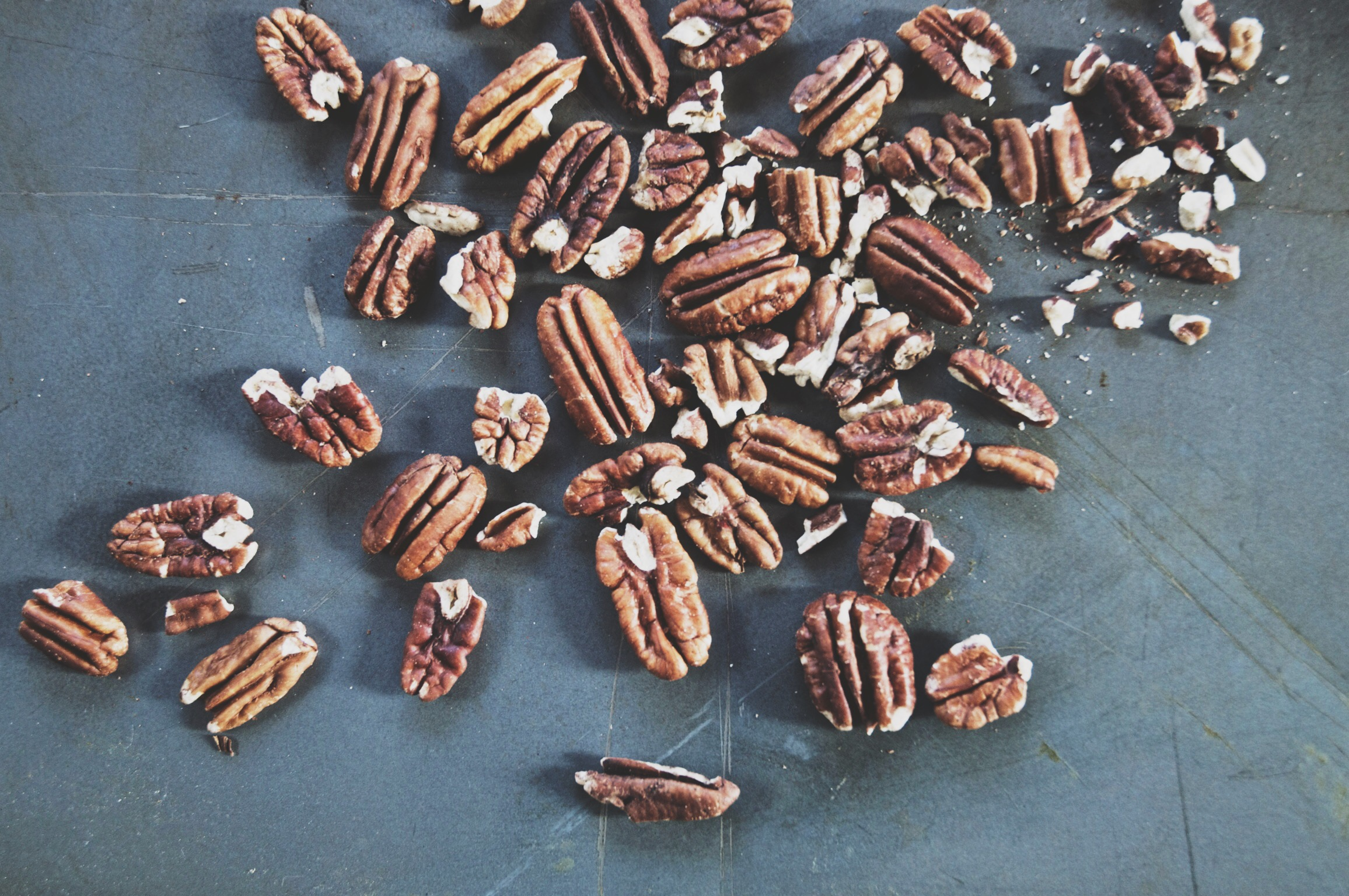 chopped and roasted pecans on a baking tin