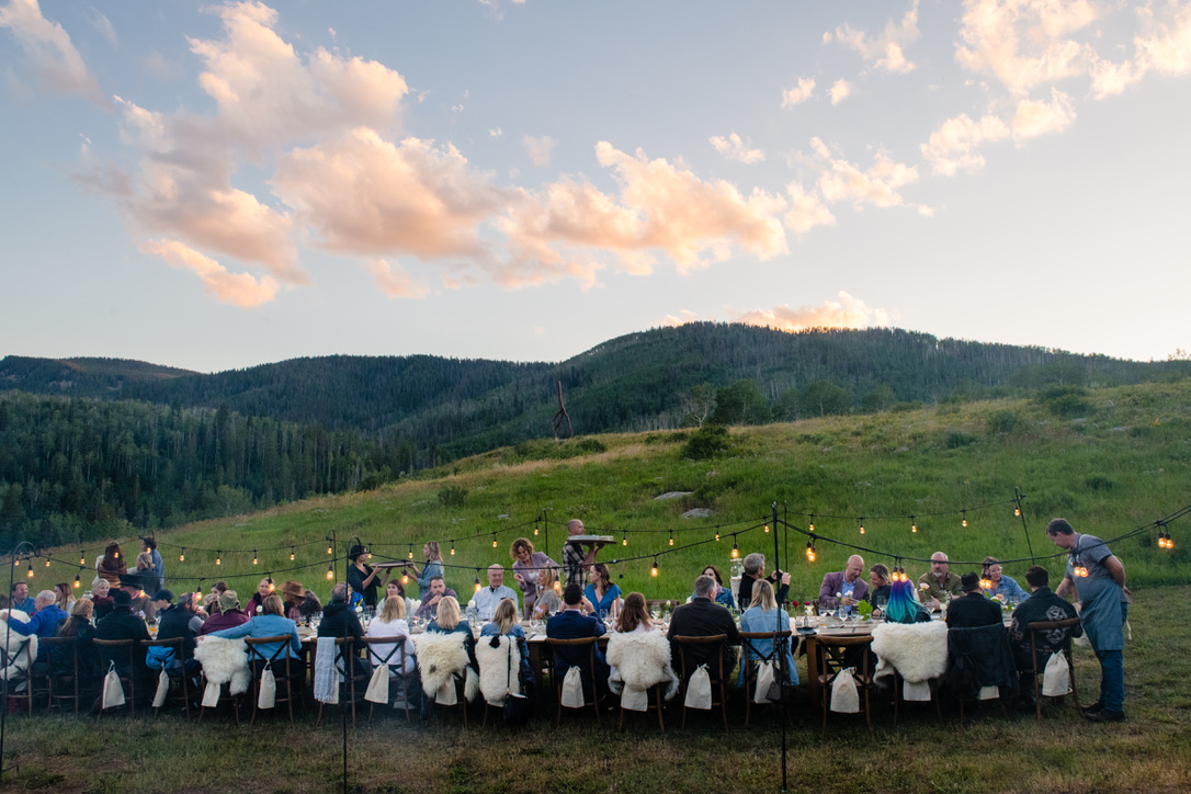 The sun is setting above the guests, as they enjoy food and wine pairings by the Colorado FIVE team.